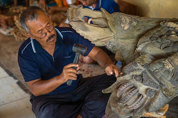 A skilled Balinese craftsman craving wooden ornaments - Bali
