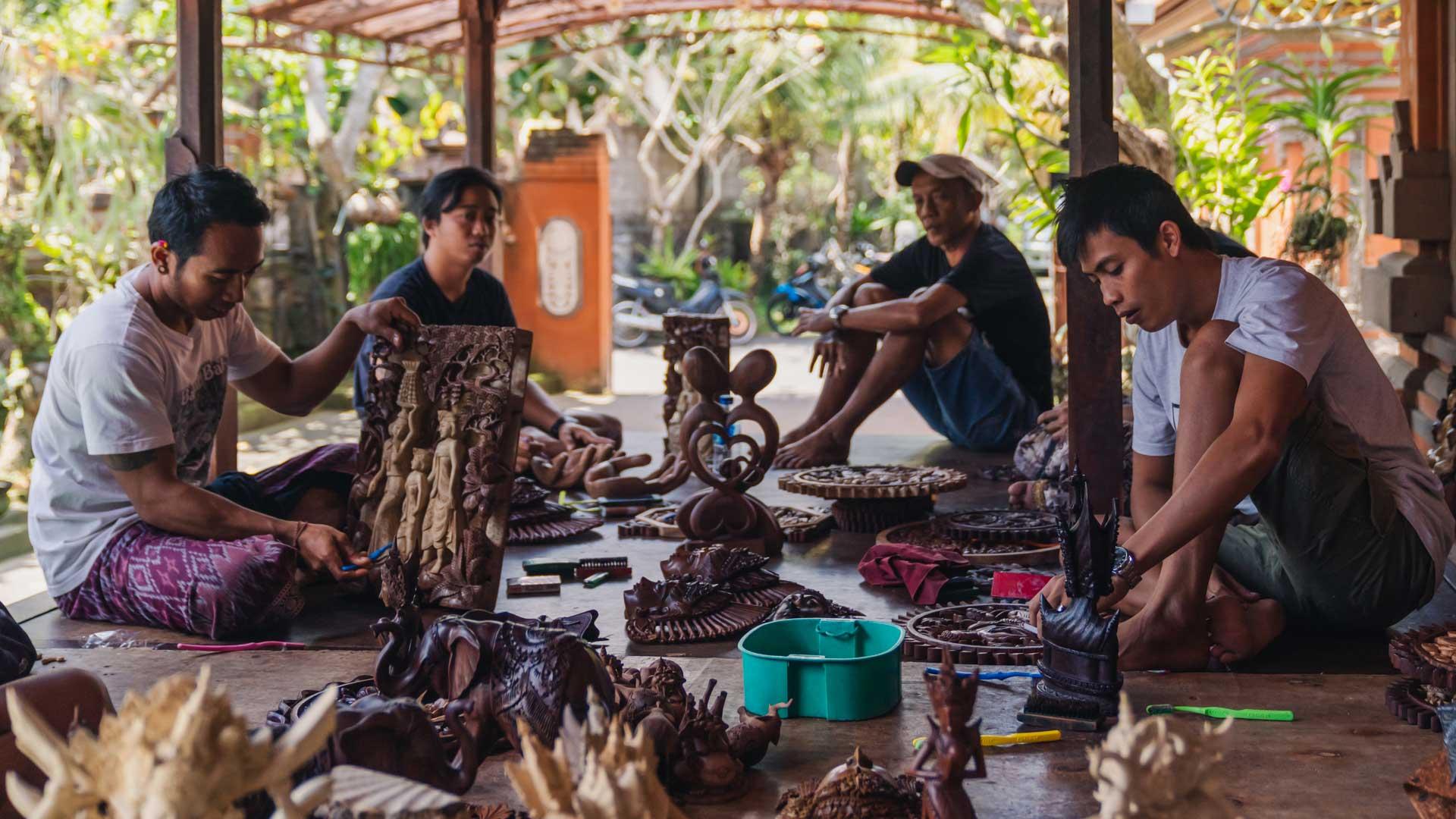 Balinese wood workers carving masks at the market - Bali