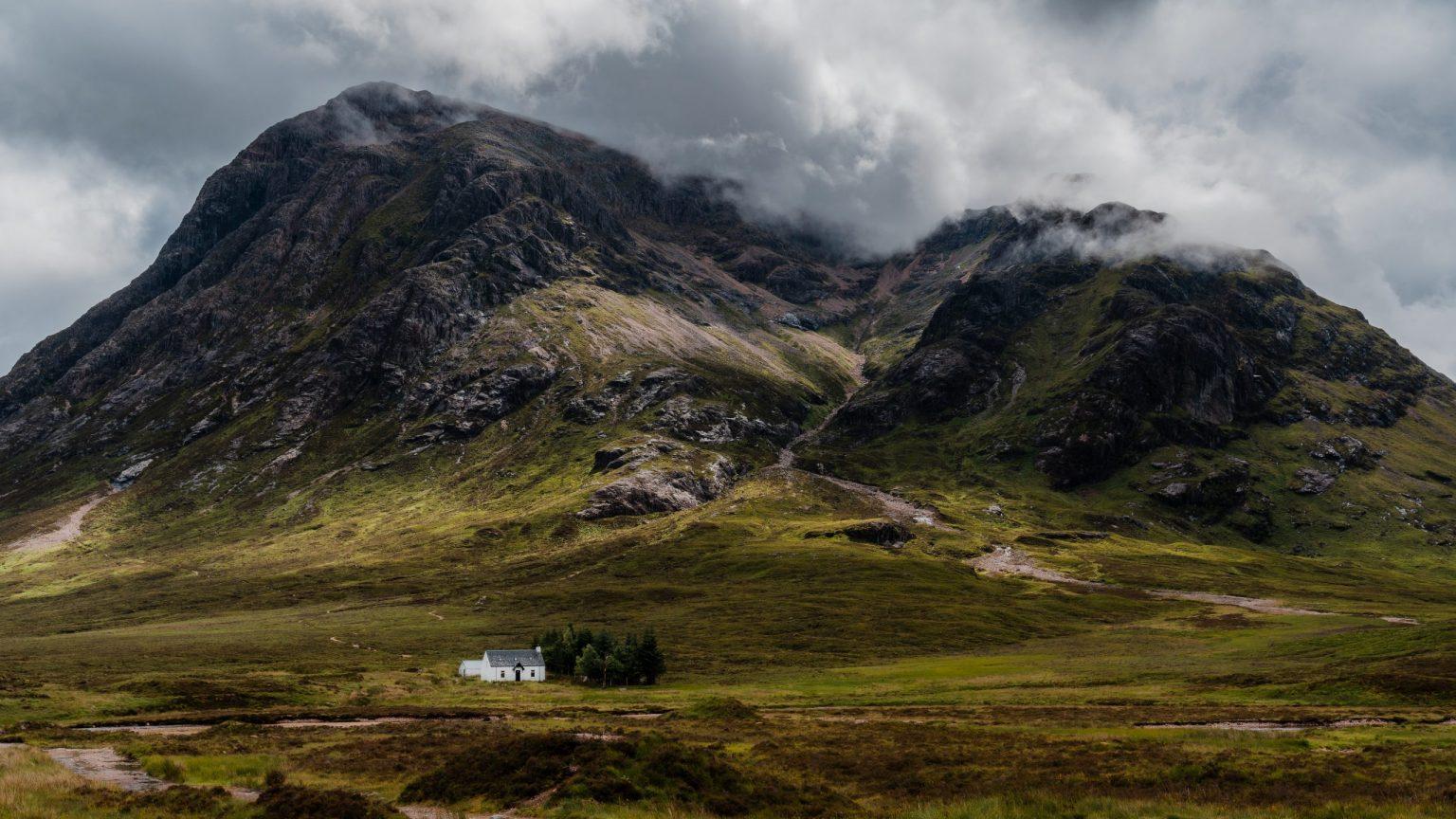 Little white house below Buachaille Etive Mòr, in Glencoe, in the Scottish Highlands in Scotland.